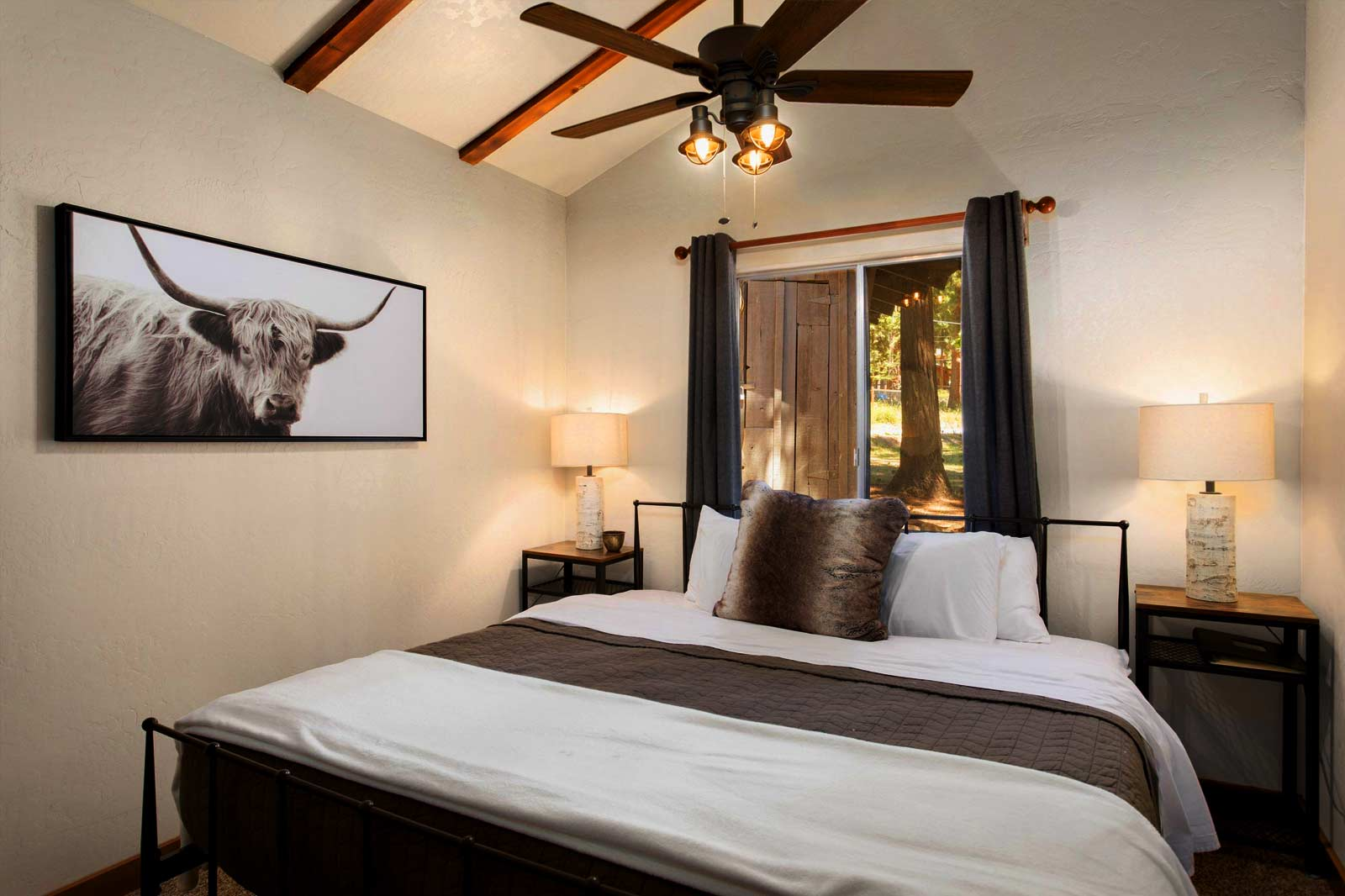 Bedroom with Queen bed and longhorn photograph on wall hanging from the Pines Cabin at Greenhorn Ranch