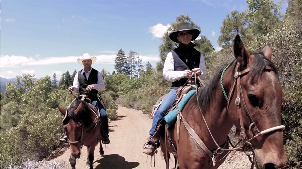 Two horseback riders on a trail ride through the Sierras in California at a dude ranch