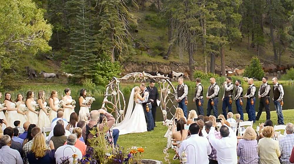A ranch, western wedding in the woods with horses loping on a trail behind the wedding party while the bride and groom kiss