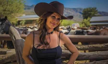 Debbe Dunning in front of a corral of horses on a dude ranch